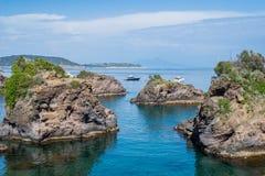 Rotseilanden in het blauwe overzees met boten - de zomervakantie Stock Afbeeldingen