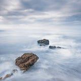 Rotsen in blauwe oceaangolven onder bewolkte hemel in een slecht weer. Stock Foto's