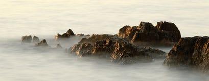 Rotsen in de golven in de zonsondergang Royalty-vrije Stock Afbeeldingen