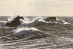 Rotsen door het ruwe overzees worden geslagen die Royalty-vrije Stock Foto's