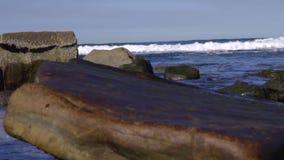 Rotsen en golven bij de oceaantrekkrachtnadruk stock footage