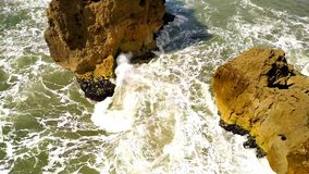 Rotsen en golven van branding in de oceaankust, in Portugese stad Nazare, Portugal stock video
