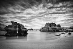Rotsen en oceaan onder een bewolkte hemel in zwart-wit Stock Afbeelding