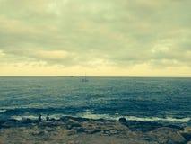 Rotsen en oceaanscène in Spanje met zeilboot in afstand Royalty-vrije Stock Afbeeldingen