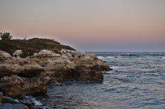Rotsen en overzees na zonsondergang Royalty-vrije Stock Afbeeldingen