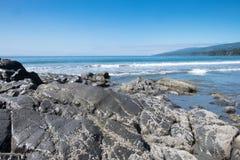 Rotsen en Vreedzame Oceaankust Stock Afbeelding
