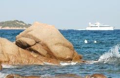 Rotsen, golven, een boot Royalty-vrije Stock Afbeeldingen