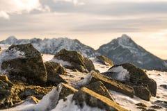 Rotsen in het ijs en zonsondergang in de bergen/oranje zonsondergang, wolken en bergen Royalty-vrije Stock Foto's