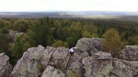 Rotsen in het midden van het bos met pijnboombomen, satellietbeeld lengte Schilderachtige mening van een mens in wit jasje stock videobeelden