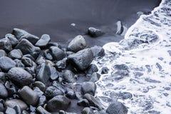 Rotsen op de zwarte zand en overzeese golven Stock Fotografie
