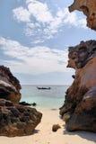 Rotsen op het strand, boot op het overzees verder Royalty-vrije Stock Afbeelding