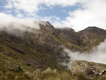 Rotsgezicht van een berg met sommige bomen, struiken en een wolk royalty-vrije stock afbeeldingen