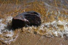 Rotsholding snel tegen golven op zandig strand Royalty-vrije Stock Afbeelding