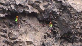 Rotsklimmers die elkaar helpen tijdens Basalt van Tungurahua-Concurrentie stock videobeelden