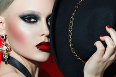 Rotsmeisje in een zwarte hoed met rode lippen stock foto's