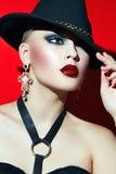 Rotsmeisje in een zwarte hoed met rode lippen stock foto