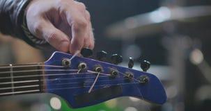 Rotsmusicus die zijn gitaar stemmen bij repetitie stock videobeelden
