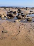 Rotspools en rotsen op het strand Stock Afbeeldingen