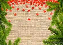 Rotsterne und Weihnachtsbaumast auf Leinenstruktur Lizenzfreies Stockbild