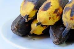 Rotte banaan in een witte schotel op witte achtergrond stock foto