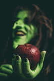 Rotten apple on a witch hand Stock Photos