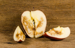 Rotten. Apple on wooden board background Stock Photos