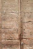 Rotten door with wormholes and pins. Detail of old wooden boards with wormholes and pins on decaying door stock image