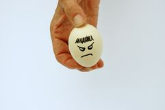 A rotten egg. Hand holding an egg with a frowning face royalty free stock photography