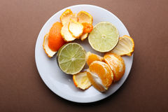 Rotten lime and peeled tangerine on plate on brown background Royalty Free Stock Photo