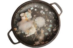 Rotten and moldy food closeup. On a pan isolated Stock Photography