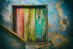 A rotten wood internal window painted in green, yellow and red Stock Photo