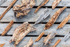 Rotten worn wooden pieces and fragments. Old rotten wooden pieces and fragments well organized on wooden plank background, top view Stock Image
