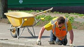 Rotterdam, holandie - Kwiecień 21 2018: Contruction pracownika naprawiać pavemant zbiory