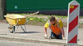 Rotterdam, holandie - Kwiecień 21 2018: Contruction pracownika naprawiać pavemant zdjęcie wideo
