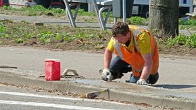 Rotterdam, holandie - Kwiecień 21 2018: Contruction pracownika naprawiać pavemant zbiory wideo