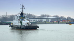 ROTTERDAM, THE NETHERLANDS - JANUARY 21, 2015: Tugboat at the harbor of Rotterdam 4K. A tugboat at the port of Rotterdam, The Netherlands. Cargo containers and stock footage