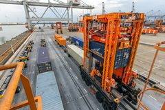 Cargo container shipping terminal. ROTTERDAM, NETHERLANDS - SEP 8, 2013: Straddle carriers moving cargo containers in the ECT shipping terminal in the Port of Royalty Free Stock Photo