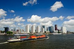 Rotterdam skyline and container ship. Rotterdam skyline and a container ship on the meuse river the Netherlands, Europe Stock Images