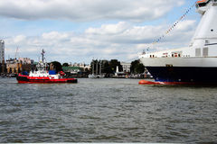 Rotterdam Tug. A tug-boat pulling a ship up the Maas river in Rotterdam Stock Photos
