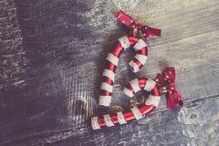 Rotting för julleksakgodis på en träbakgrund i formen av en hjärta fotografering för bildbyråer