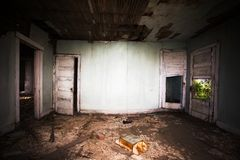 The rotting interior of a room in abandoned home. Broken doors and rotting plaster on ceiling with garbage on the floor of an abandoned home Royalty Free Stock Images
