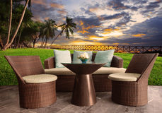 Rottingstolar i utomhus- terrassvardagsrum mot härligt s Royaltyfri Bild