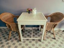 Rottingstolar och vit wood tabell i rum royaltyfria foton