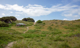 Rottnest Hills. Remote narrow trail with old building and grassy coastal dunes under a blue sky with clouds at Rottnest Island in Western Australia Stock Photos