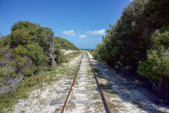 Rottnest Railroad. Railway through the lush dunes with native trees at Rottnest Island with a turquoise Indian Ocean seascape on a sunny day in remote Western Royalty Free Stock Images