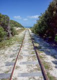 Rottnest Railway. Railway lines through the native coastal trees at Rottnest Island with a turquoise Indian Ocean seascape on a sunny day in remote Western Stock Photography