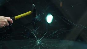 Rottura del vetro dell'automobile con un martello video d archivio