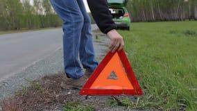 Rottura dell'automobile Il tipo mette un triangolo rosso sul bordo della strada archivi video