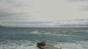 Rottura delle onde del mare sul pilastro di pietra stock footage