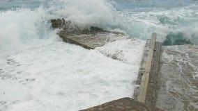 Rottura delle onde del mare sul pilastro di pietra Movimento lento stock footage